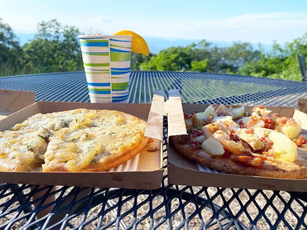 Photo by user deity.dreams, caption reads Personal pizzas and cocktails with a view of @shenandoahnps..#bigmeadows #skylinedrive #shenandoahnationalpark #ohshenandoah #bigmeadowslodge #pizza #views #dateday