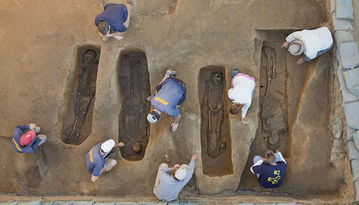Overview of the chancel burial excavations. Archaeologists (from left to right) Mary Anna Richardson, Danny Schmidt, David Givens, Dan Smith, Don Warmke, Jamie May, Dan Gamble, and Dr. William Kelso. Photo by Michael Lavin, Courtesy of Jamestown Rediscovery Foundation (Preservation Virginia)